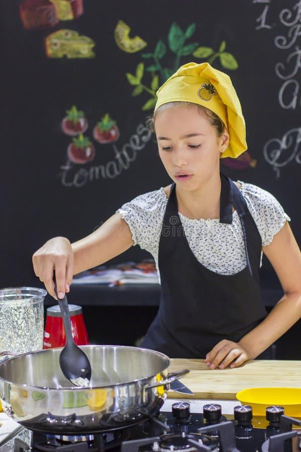 厨师` s帽子的女孩在黑色的大平底深锅烹调 免版税图库摄影