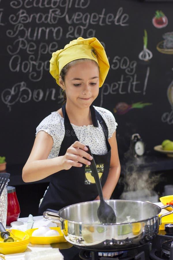 厨师` s帽子的女孩在黑色的大平底深锅烹调 库存图片