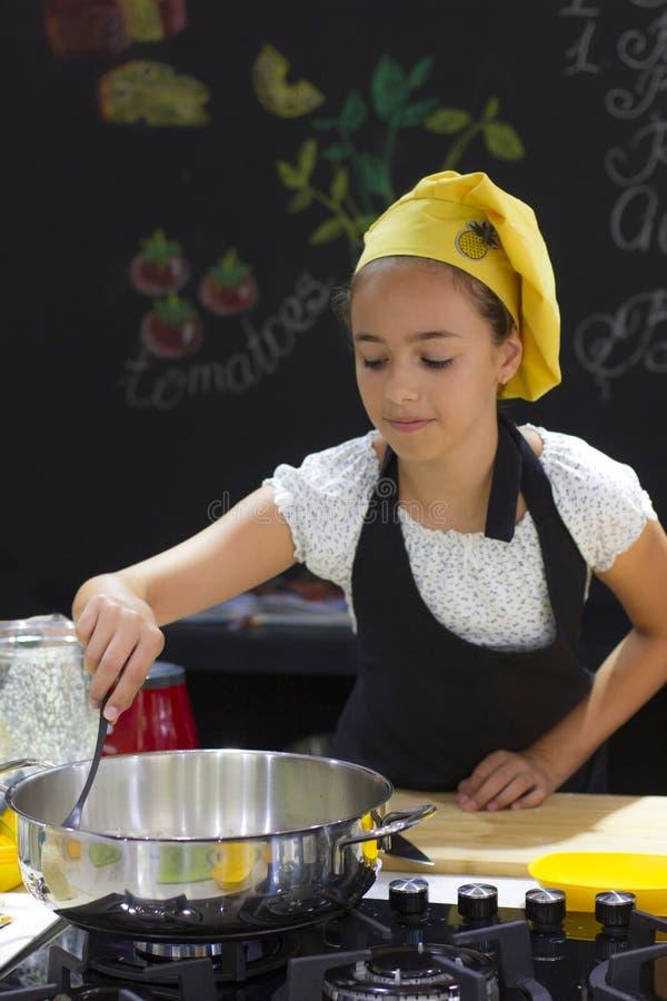厨师` s帽子的女孩在黑色的大平底深锅烹调 图库摄影