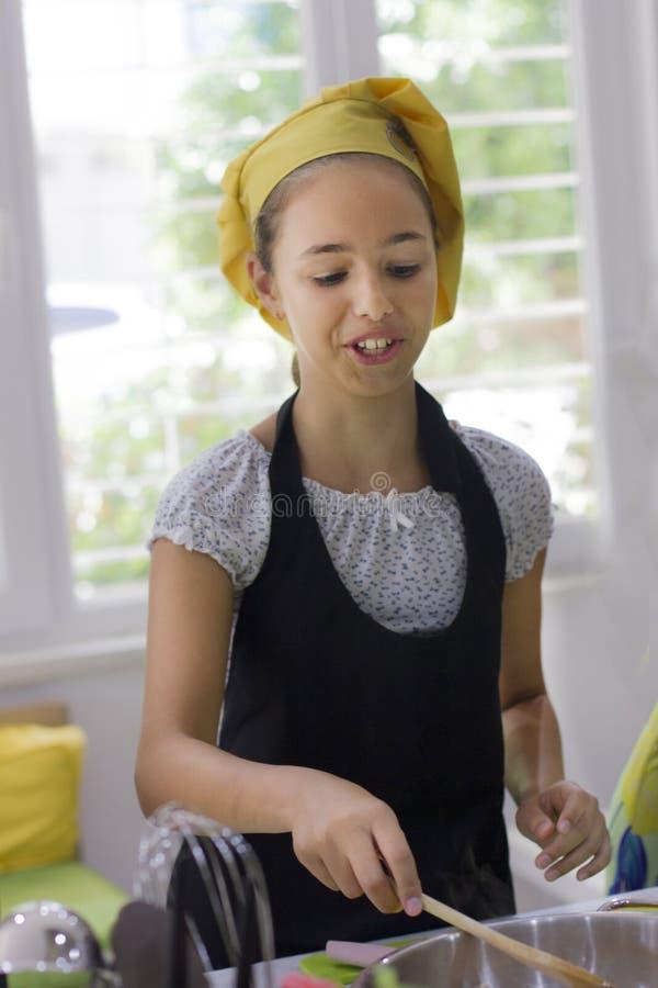 厨师` s帽子的女孩在黑色的大平底深锅烹调 免版税库存图片