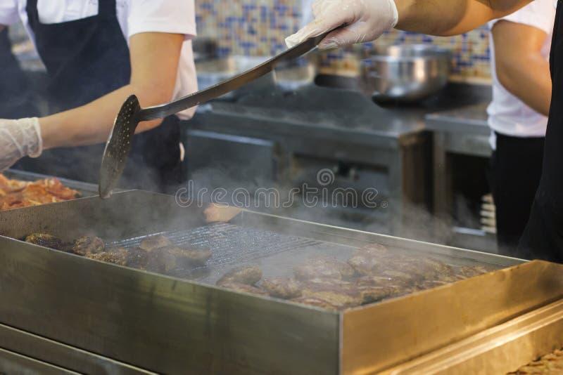 厨师` s手油煎在一个通入蒸汽的格栅的肉和汉堡炸肉排 免版税图库摄影