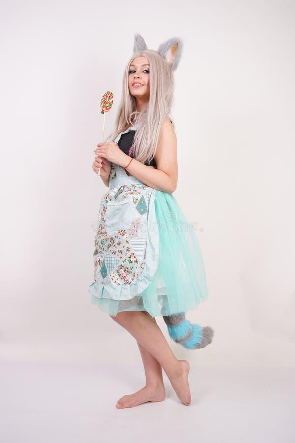 厨房围裙的迷人的白种人全部赌注十几岁的女孩与在白色演播室背景的五颜六色的棒棒糖 免版税库存图片