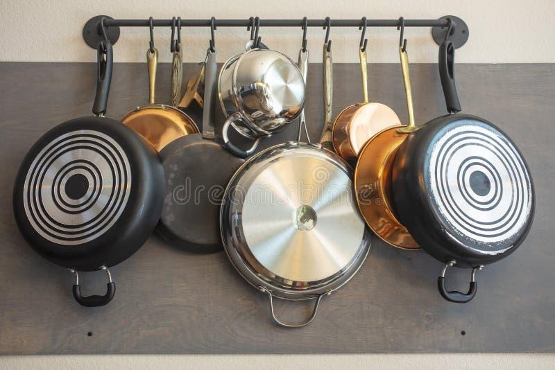 厨房垂悬的罐、平底锅、围裙和其他器物的墙壁机架存贮和装饰的 库存照片