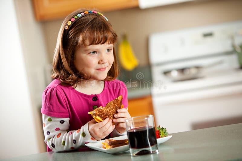 厨房女孩:吃烤乳酪 免版税库存照片
