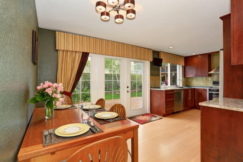 厨房室内部连接用与深绿墙壁的饭厅 图库摄影