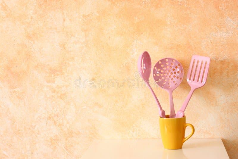 厨房炊事用具。在黄色杯子的塑料小铲对土气赤土陶器墙壁。 库存图片