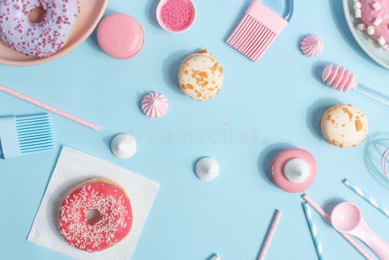 厨房用具和工具、酥皮点心和甜点在蓝色背景 顶视图 复制空间 图库摄影