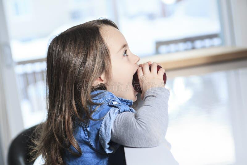 厨房的儿童女孩用苹果 免版税图库摄影