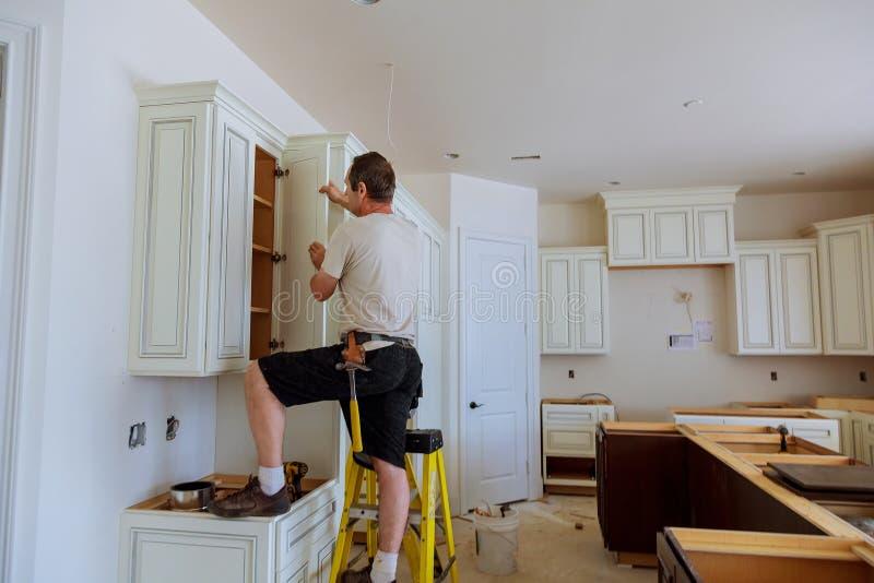 厨房的设施 工作者安装门到厨柜 库存图片