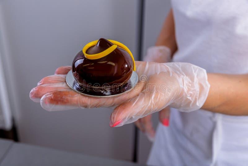 厨房釉酥皮点心的点心师 厨师展示一个完成的巧克力给上釉的蛋糕 主要类在厨房里 库存照片