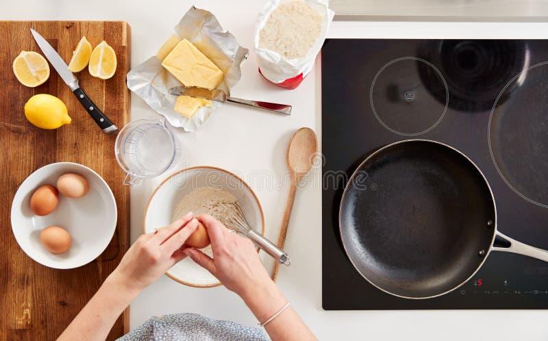 厨房里女人的头像,配着煎饼或薄饼的配料 免版税图库摄影