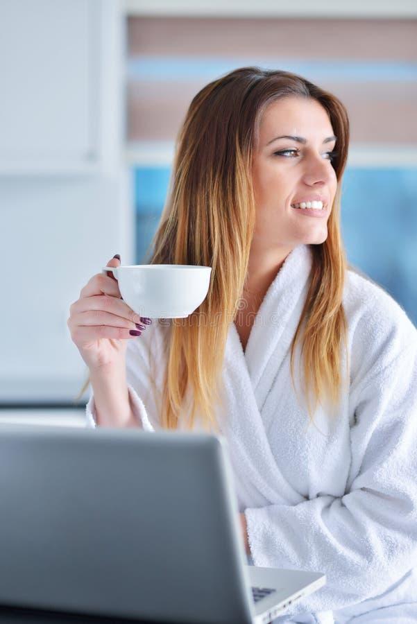 厨房读书的愉快的妇女他在她的膝上型计算机的新闻 免版税库存照片