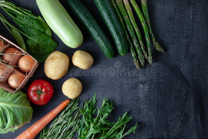 厨房-新鲜五颜六色有机,在黑暗的石背景的春天菜 红萝卜、蕃茄、荷兰芹、芦笋和迷迭香舱内甲板 免版税库存照片