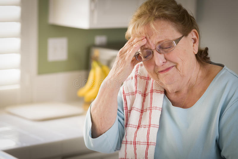 厨房水槽的哀伤的哭泣的资深妇女 免版税库存照片