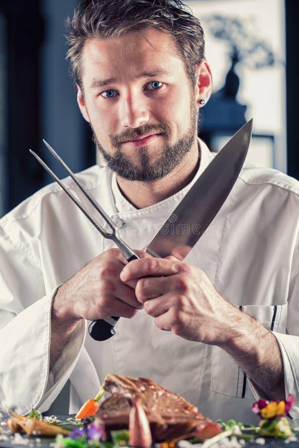 主厨 滑稽的厨师 有横渡的刀子和叉杆的厨师 专业厨师在餐馆或旅馆准备或切开丁骨牛排 免版税库存照片