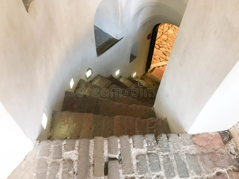 去下来从步的陡峭的石螺旋台阶 免版税库存图片