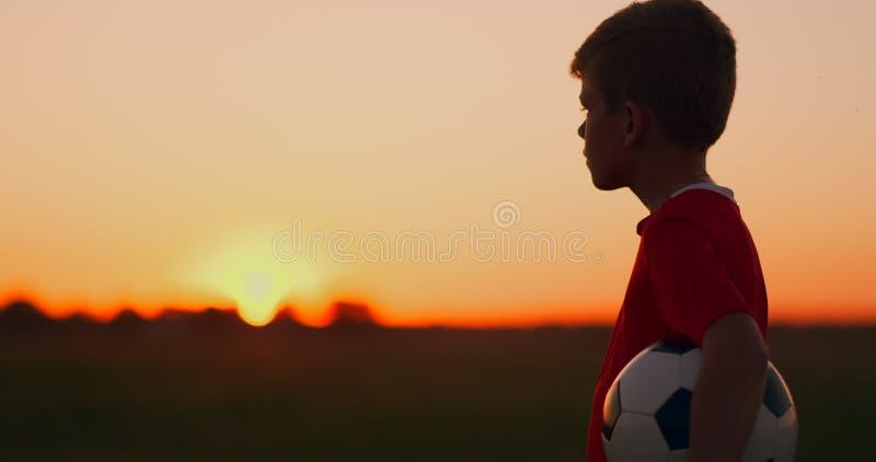 去与在领域的球作梦橄榄球事业的年轻足球选手,在看太阳的日落 库存图片