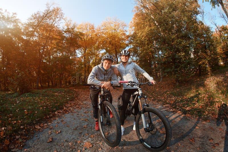 去为自行车的愉快的年轻夫妇在一秋天天乘坐在公园,背后照明 图库摄影