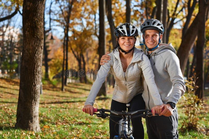 去为自行车的愉快的年轻夫妇在一秋天天乘坐在公园 库存图片