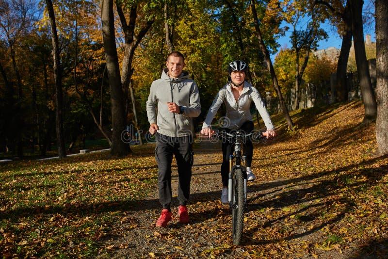 去为自行车的愉快的年轻夫妇在一秋天天乘坐在公园 库存照片