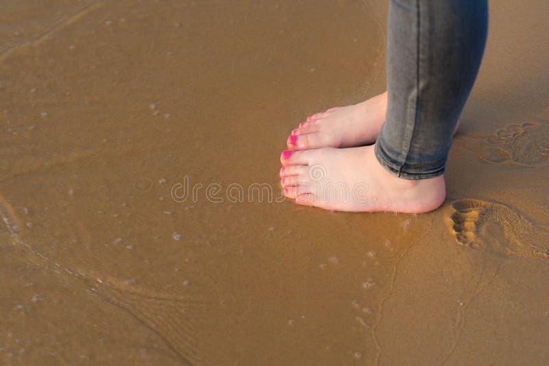 去在夏天海滩的年轻女人脚 少年走的接近的腿海,在海滩的沙子 r 库存照片