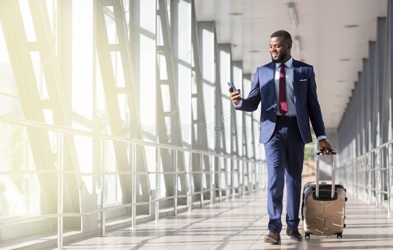 去在飞机上 商人运载的行李,移动向登机门在机场 库存照片