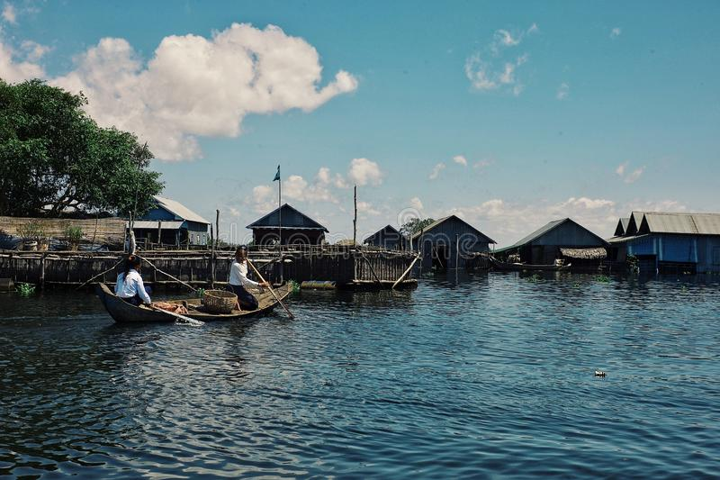 去地方的少女教育与在湖的一个传统独木舟 库存照片