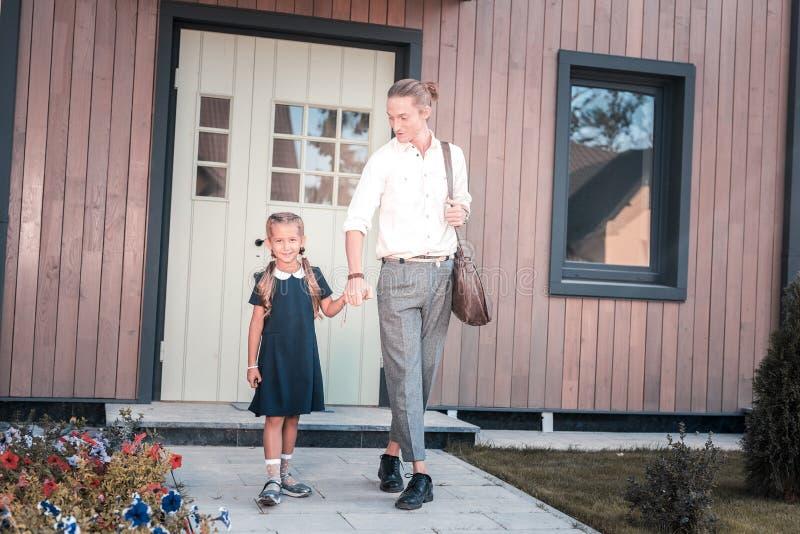 去她的年轻的父亲的快乐的逗人喜爱的女小学生藏品手教育 库存照片