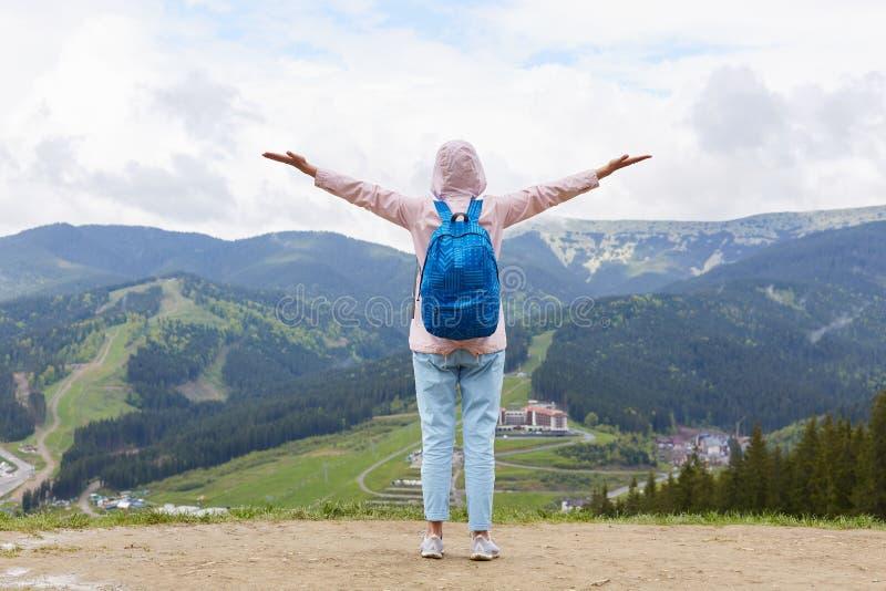 去嬉戏女孩的徒步旅行者全长射击山,站立与胳膊被舒展对享受风景的天空,佩带 免版税库存照片