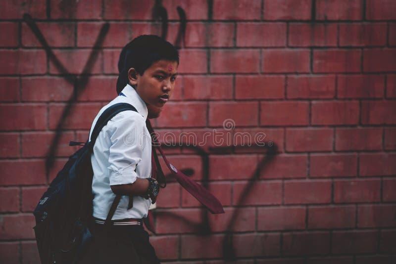去学校穿戴制服和红色领带的尼泊尔男孩在Thamel S 库存图片