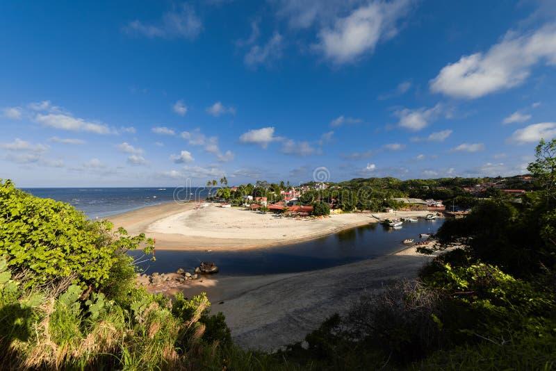 去峭壁的边缘的一个人,一个能看到海滩和某一房子 免版税库存图片