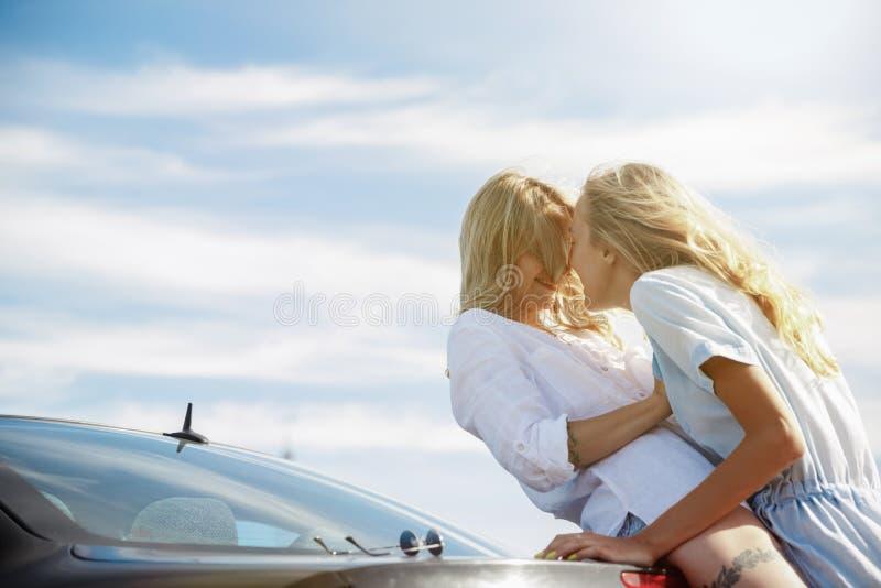 去年轻女同性恋者的夫妇假期在汽车的旅行在好日子 免版税库存照片