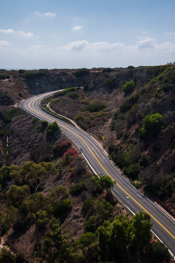 去弯曲的双线的路山 汽车或人不存在 库存照片