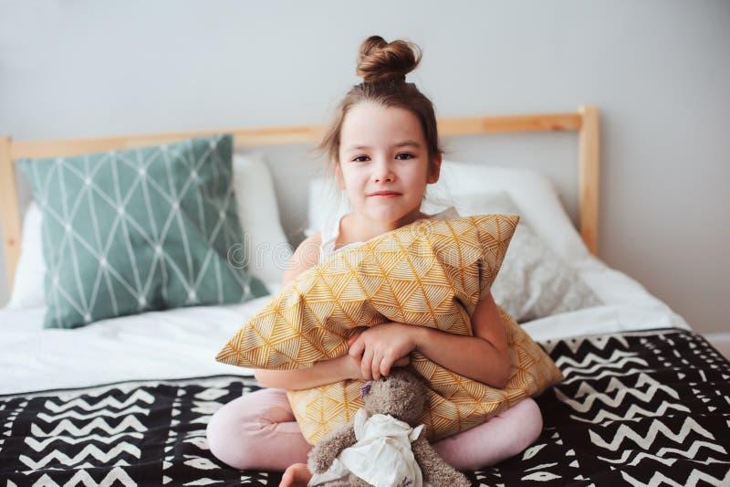去愉快的儿童的女孩坐床和拥抱把枕在,醒在清早或睡 库存图片