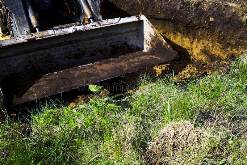 去泥泞的挖掘机的桶开掘在象草的领域的土壤在乡下 免版税库存图片