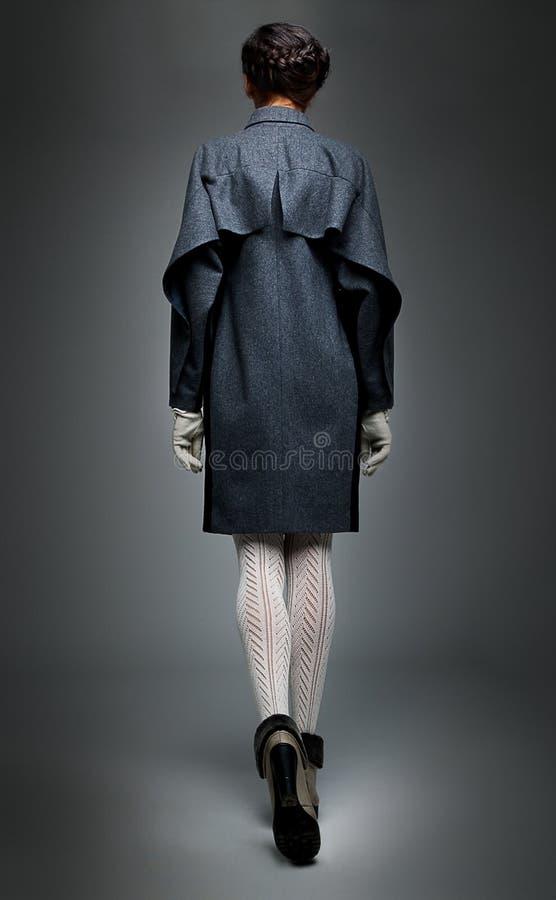 去深色的外套方式灰色模型走 免版税库存图片