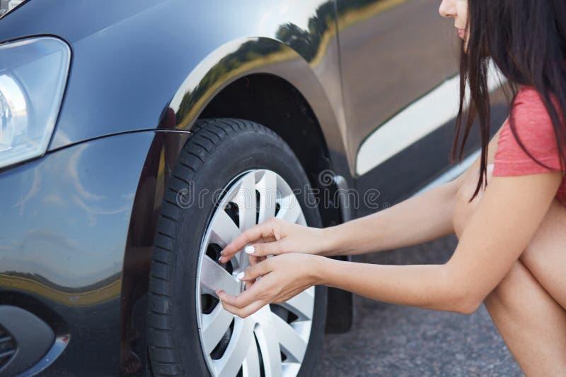 去深色的母的司机播种的射击更换平车轮胎,有在路的问题,没有帮助的人近,尝试对solv 库存照片