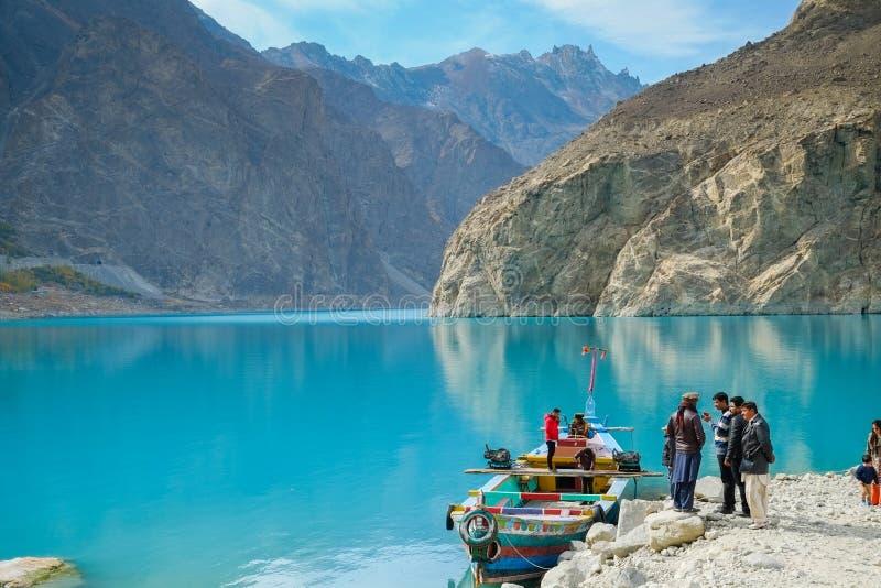 去的人们在Attabad湖租用小船,以山背景为目的 图库摄影