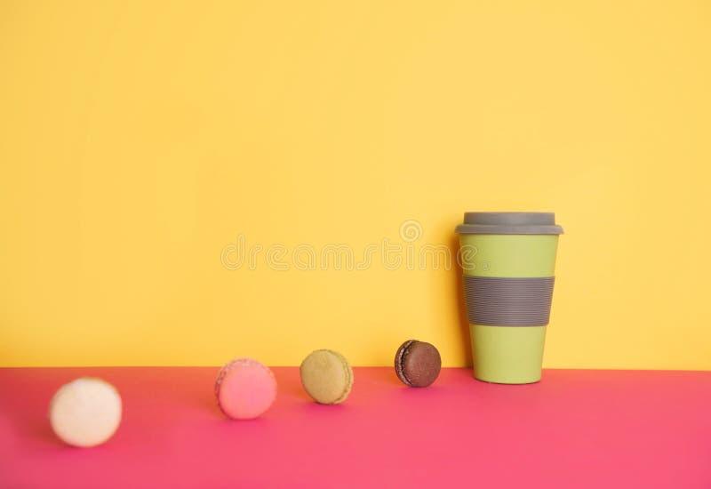 去的咖啡用在黄色和桃红色背景的蛋白杏仁饼干 免版税库存照片