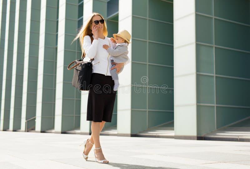 去的妇女工作与婴孩在她的手上 免版税图库摄影