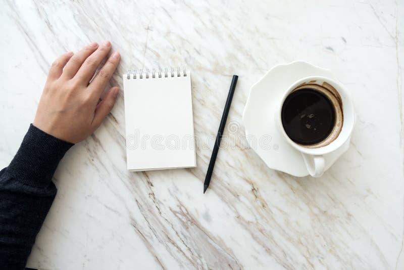 去的手写下在有咖啡杯的一个空白的白色笔记本在桌上 免版税库存图片