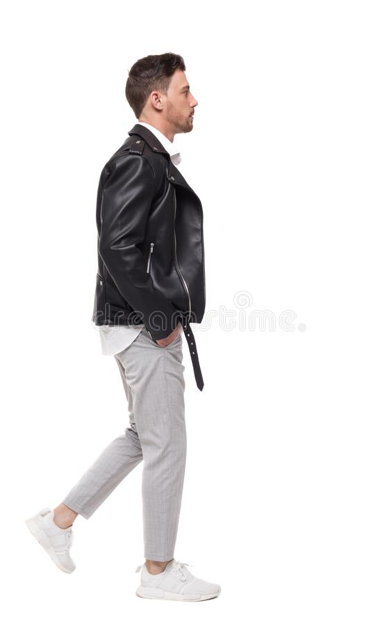 去的英俊的人侧视图一个皮夹克和裤子的 免版税库存照片