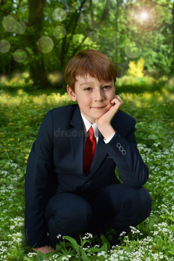 去第一圣餐的男孩室外画象 库存照片