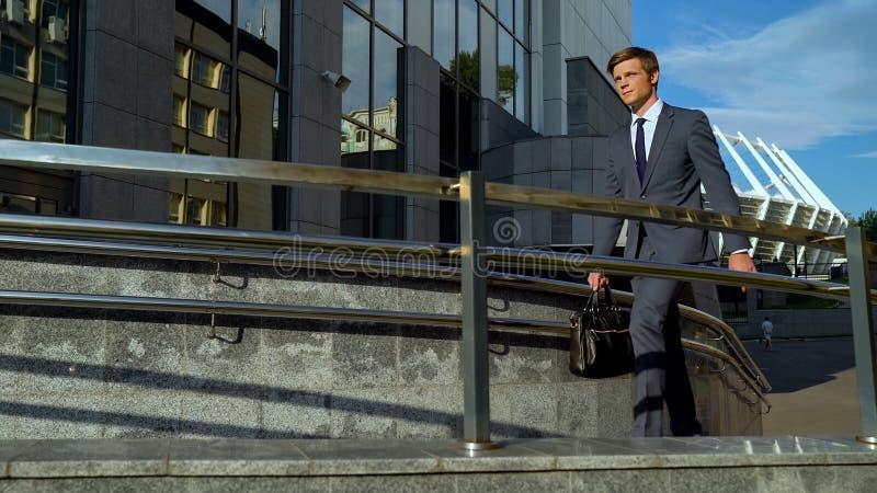 去英俊的年轻依据自决的办公室经理工作,大厦事业 免版税库存照片