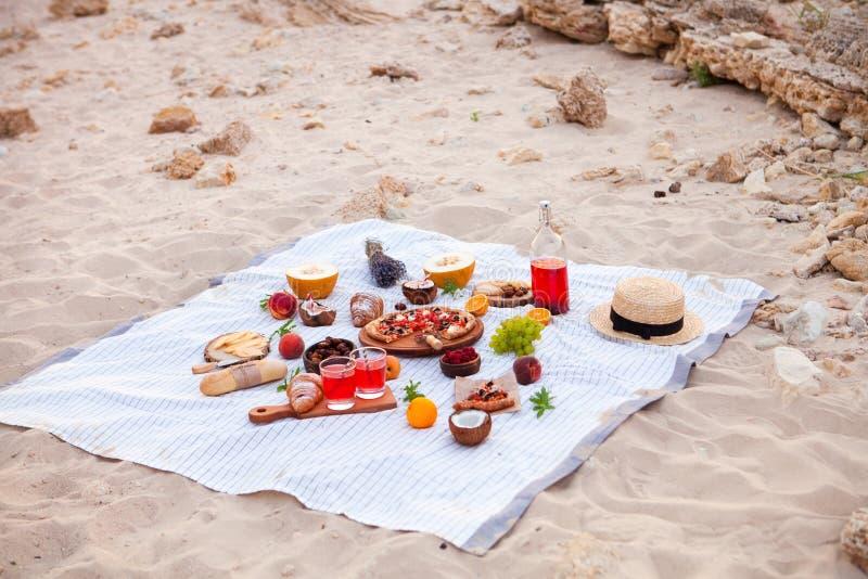 去野餐在海滩在白色格子花呢披肩、食物和饮料的日落 库存照片