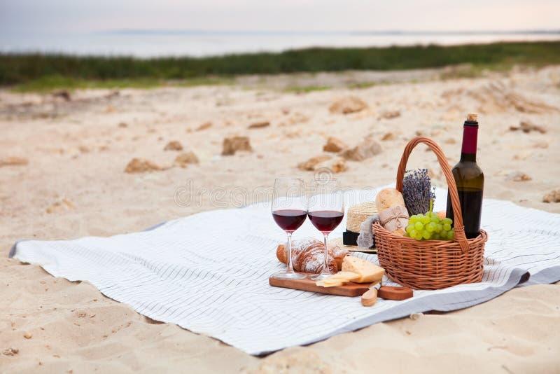 去野餐在海滩在白色格子花呢披肩、食物和饮料的日落 库存图片