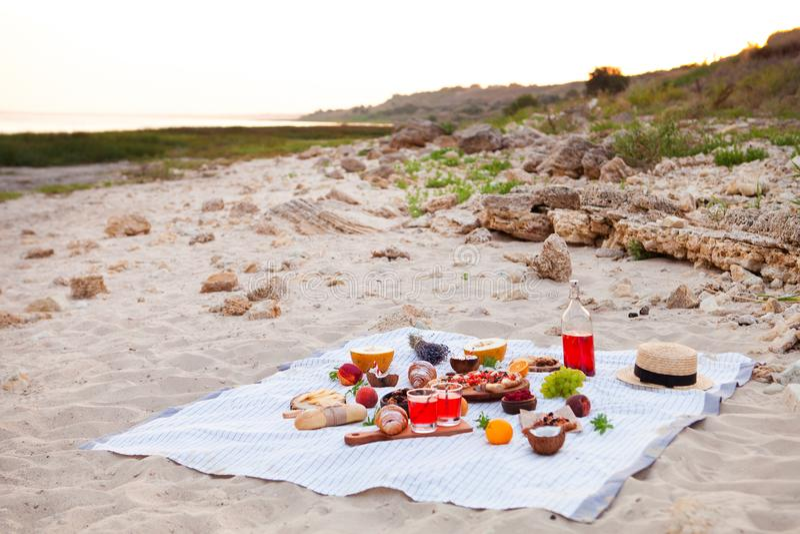去野餐在海滩在白色格子花呢披肩、食物和饮料的日落 免版税库存照片