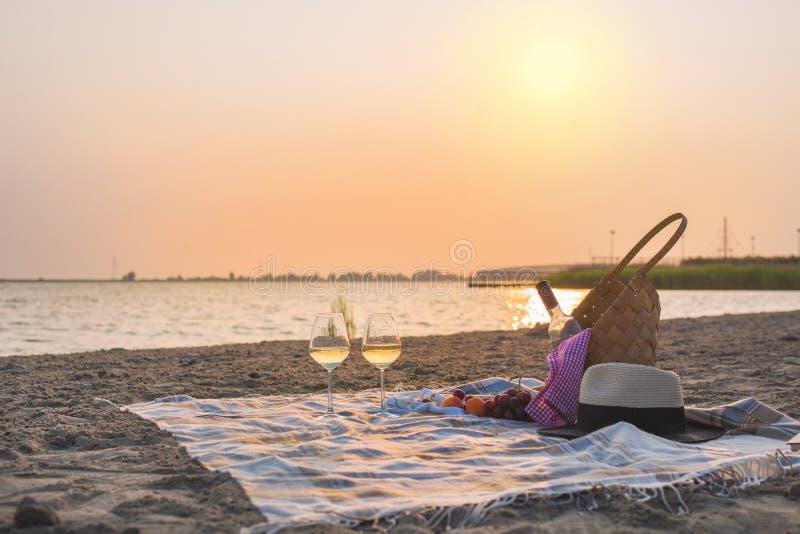 去野餐用在海滩的酒由海 在日落的浪漫晚餐 复制空间 免版税库存图片