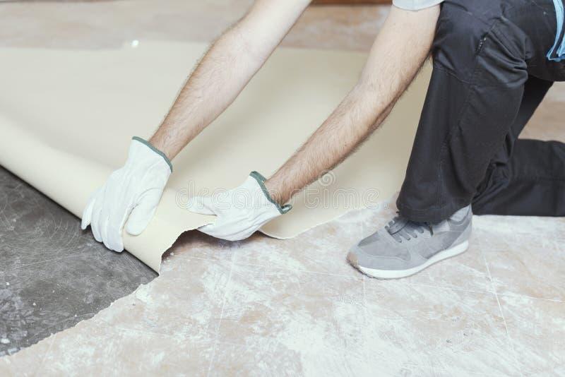 去除一块老亚麻油地毡地板的承包商 免版税库存照片