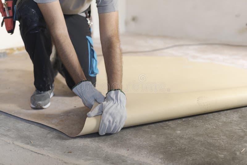 去除一块老亚麻油地毡地板的承包商 库存图片